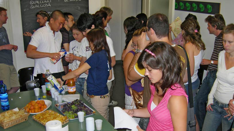 Foreign students socialising while enjoying fruits, sweets and soft drinks